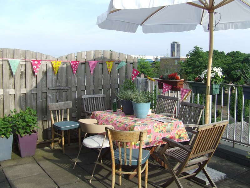 eclectic patio idea with elegant grey fences decorated by colorful flag strings different style seats concrete decking idea