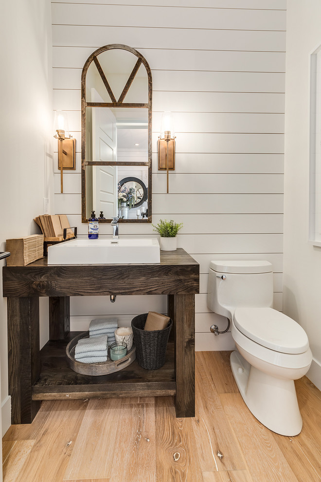 farmhouse bathroom vanity reclaimed vanity mirror a couple of vanity light fixtures white sink dark finishing vanity countertop medium toned wood floors