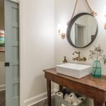Farmhouse Bathroom Vanity With Rustic Appeal Wood Countertop Vessel Sink In White Metal Basket For Storage Round Mirror With Black Frame And Chain