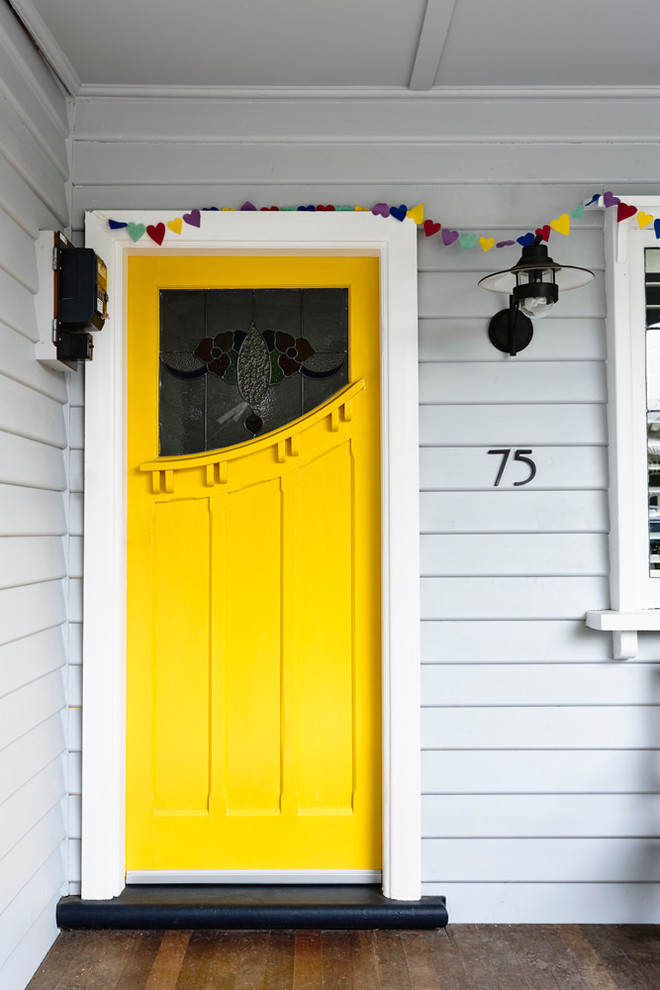lime yellow contemporary colonial front door with asymmetric window accent white siding exterior walls dark toned wood floors