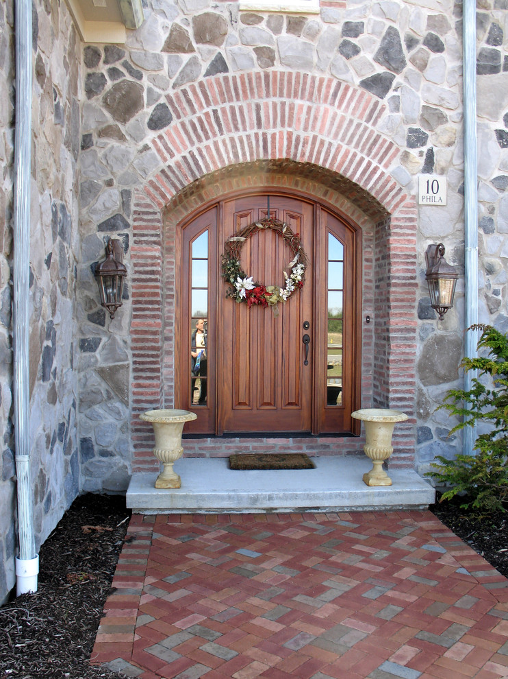 mediterranean colonial front door with reflective sidelights and wreath bricks walkway lantern wall sconces
