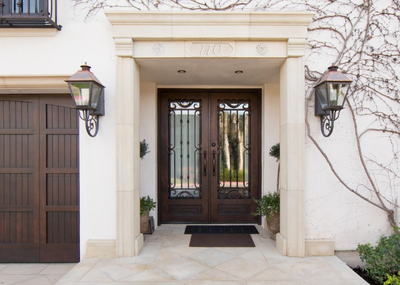 mediterranean entryway colonial front door with reflective mirror panels and black wrought iron rails light cream stucco exterior walls mediterranean style wall sconces