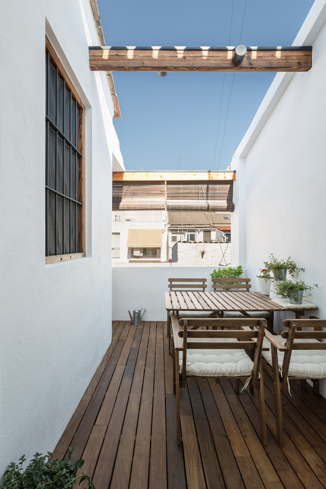 mediterrenean balcony with higher walls wood decking floors wooden outdoor furniture set with white tufted seaters