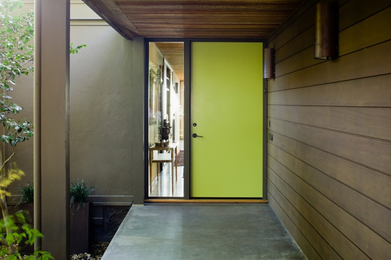 mid century modern front door in lime yellow large sidelight with black doff trims concrete floors