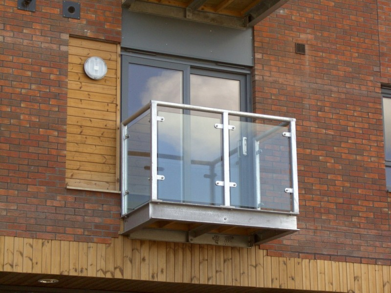 modern balcony for small apartment made of steel and supported by tough glass panels and durable metal rails