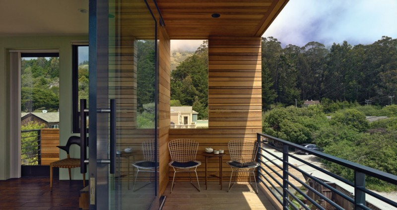 modern balcony idea wood siding exterior wall wood decking floors black stained metal railing system a couple of lightweight metal chairs high legs and small side table