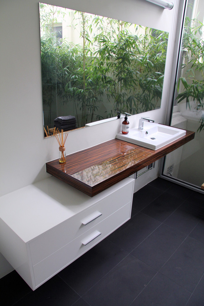 modern minimalist bathroom vanity with bamboo countertop white sink floating white cabinets blue stone tiles flooring