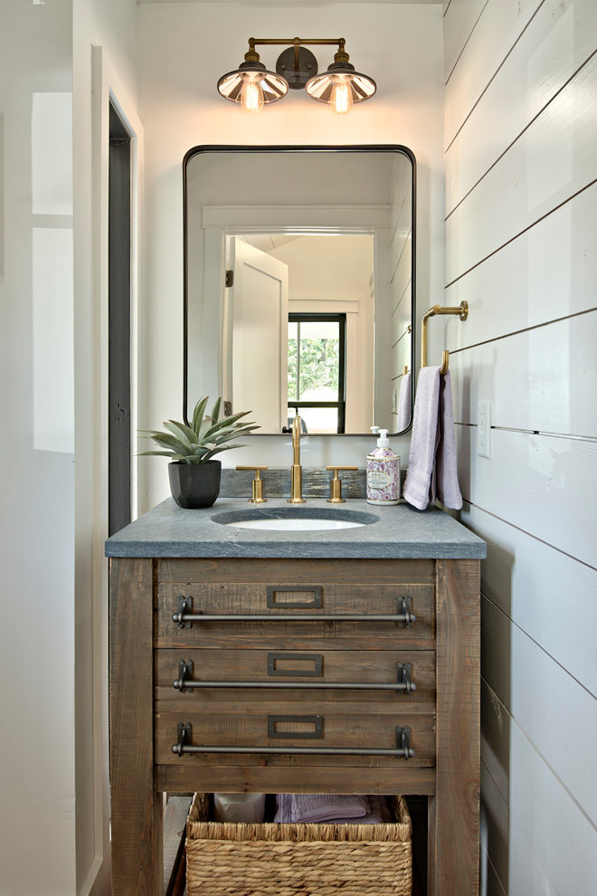 modern rustic bathroom vanity dark wood cabinets with hard metal handlers stone countertop white undermount sink gold toned faucet black framed mirror rustic style vanity lamps