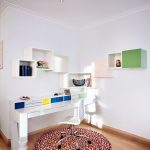 Modern Working Space Bespoke Shelves Idea White Freestanding Working Desk With Bright Colored Drawers Movable Working Chair In White Multicolored Area Rug In Round Shape Medium Toned Wood Floors