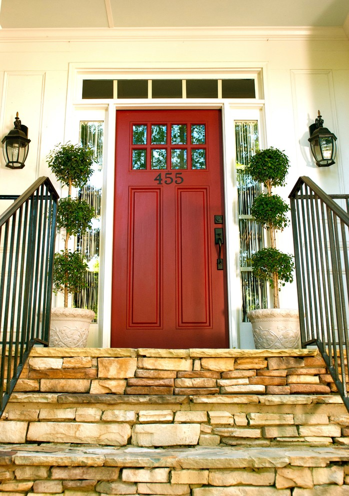 pop red colonial front door with side windows and transom a pair of planters with decorative green plants
