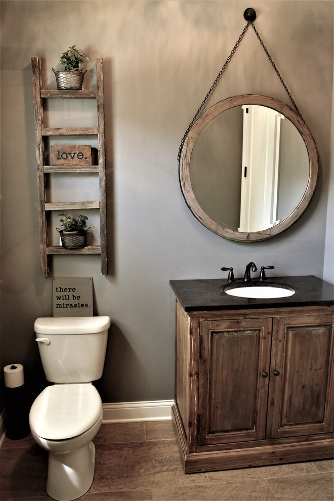rustic powder room idea old and shabby wood cabinets marble countertop with small undermount sink rounded mirror with shabby wood frame and hanging chain shabby & old ladder shelves on wall