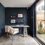 Scandinavian Style Home Office Dark Blue Walls White Ceilings Beige Ceramic Floors Blue Sea Working Desk Modern Working Chair Modern Black Working Light Fixture Black Floating Shelves
