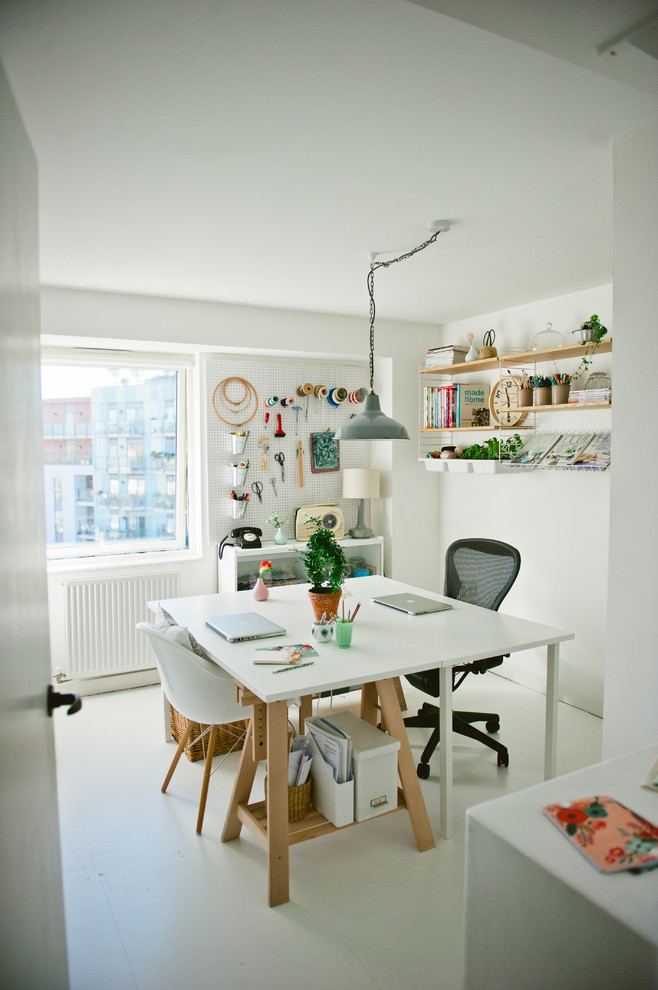 scandinavian style home office larger white working desk black working chair with wheels white mid century modern side chair with wood legs wood floating shelves lightweight metal net wall organizer