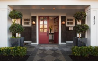 scralet colonial front door with glass panels black exterior walls with white trimmed exterior windows giant planters concrete floor entryway with diamond cut motifs