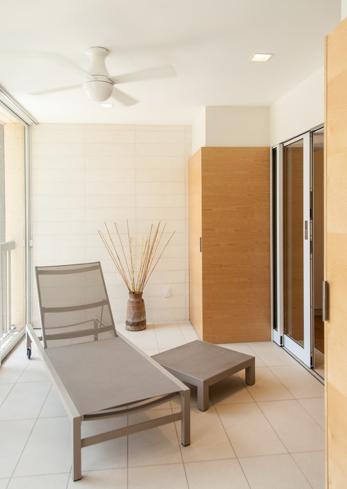 small balcony for apartment white tiles flooring white subway tiles walls birch paneled closets sliding glass door light grey furniture set ceiling fan