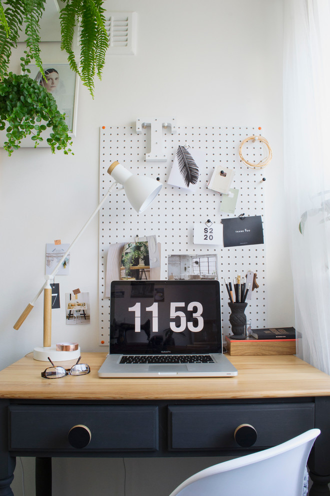 small home office idea wood top working desk with drawers white pegboard with dark dots decoration white walls some greeneries