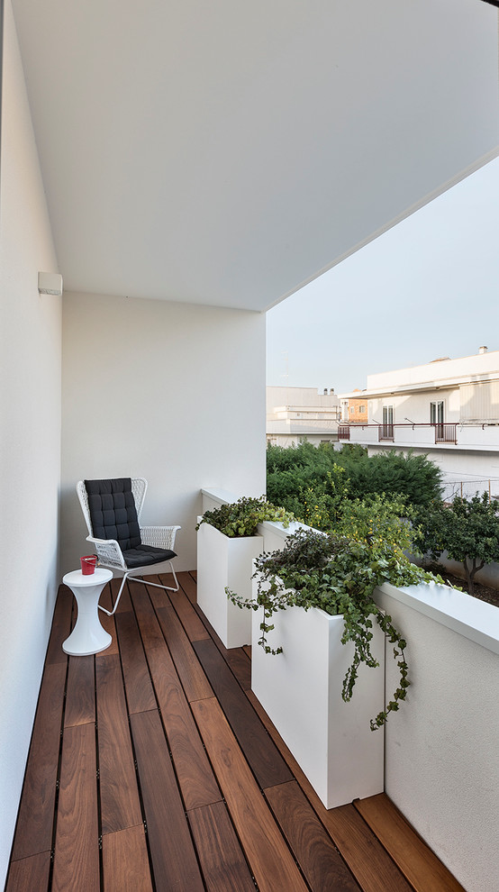 small modern balcony white painted concrete walls and ceilings wood decking floors permanent concrete planters modern chair small sized side table in white