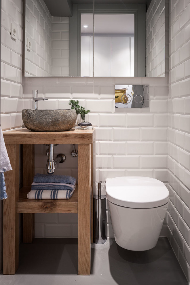 small sized Scandinavian style powder room white subway ceramic tiles walls grey laminate floors hard stone vessel sink wooden countertop and open shelf wall mounted toilet in white
