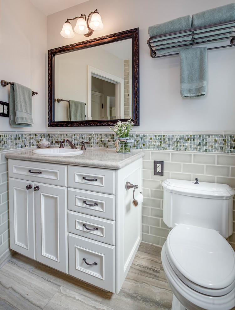 traditional bathroom vanity with light neutral color palette handcarving framed mirror traditional vanity lamps on top undermount sink toilet mosaic tiles backsplash