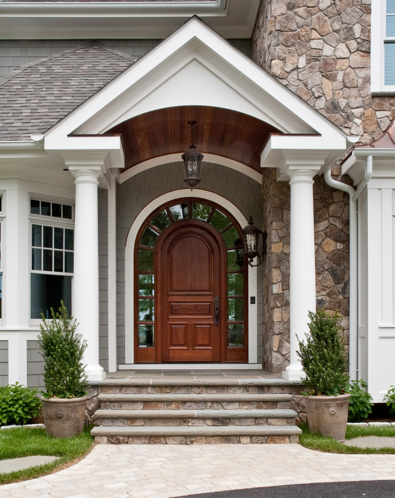 traditional exterior design curved top colonial front door with curved top glass sidelights grey shingles door's background stones exterior walls traditional black wrought iron sconces