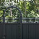Traditional Wood Fence System In Grey With Curved Detail On Gate's Top