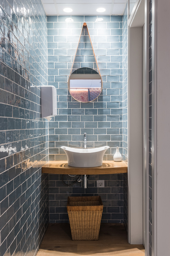 very small scandinavian powder room blue aquatic subway ceramic tiles walls hanging round mirror higher vessel sink in white wood countertop basket for storage solution