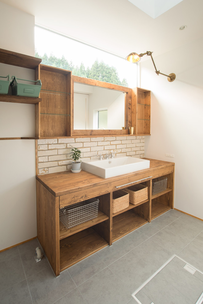 wood bathroom vanity idea wood countertop farmhouse sink in white white bricks look like laminate backsplash wood framed mirror with open shelves in either side