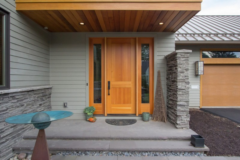 wood colonial front door with side glass windows grey siding exterior walls slate floor entryway slate base exterior walls