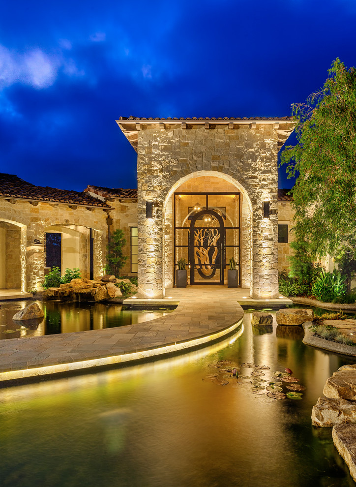 Mediterranean exterior idea wall sconces on entrance rope light on pool textured stone exterior walls paving pathway