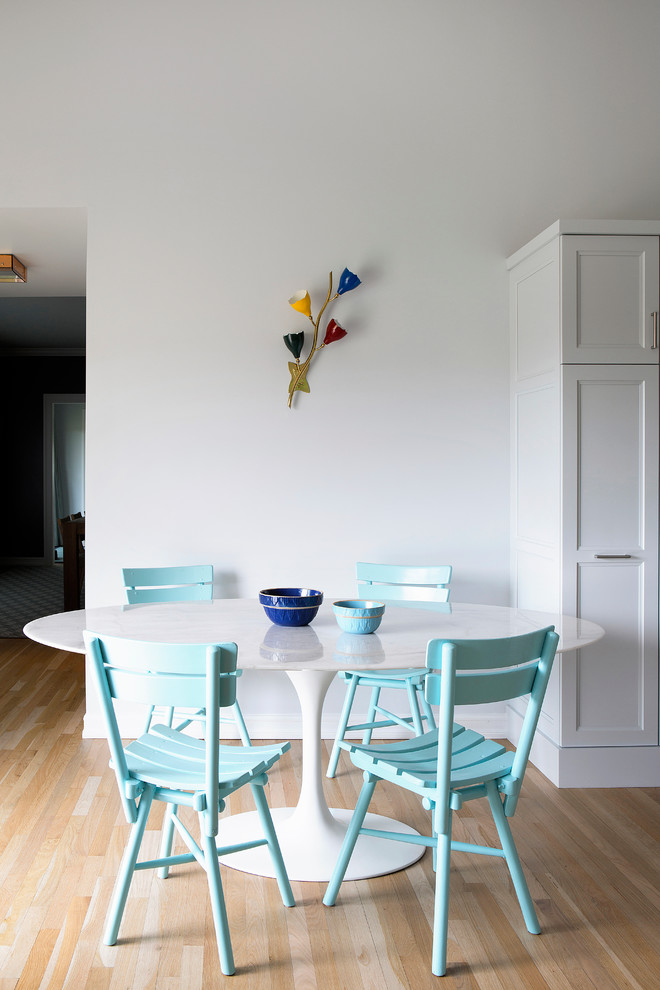blue dining chairs round top dining table in white white walls light toned wood floors