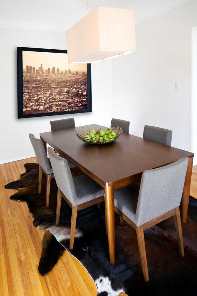 clean look and modern line dining room grey upholstered dining chairs dark wood dining table layered dark cowhides oversized photograph fabric pendant medium toned wood floors