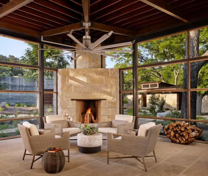contemporary sunroom standard ceilings in dark corner fireplace with soft neutral surrounds soft neutral chairs concrete floors dark trimmed glass windows