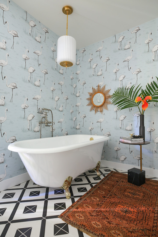 eclectic bathroom idea light blue wallpaper with decorative swan motifs gold toned claw foot bathtub decorative mirror tuscan area rug tiny side table modern pendant lamp