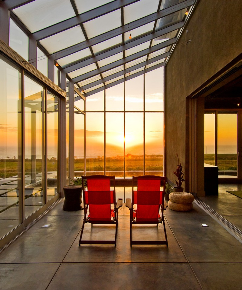 grand modern sunroom in coastside house modern red outdoor chairs semi slanted glass roofs glass wall panels