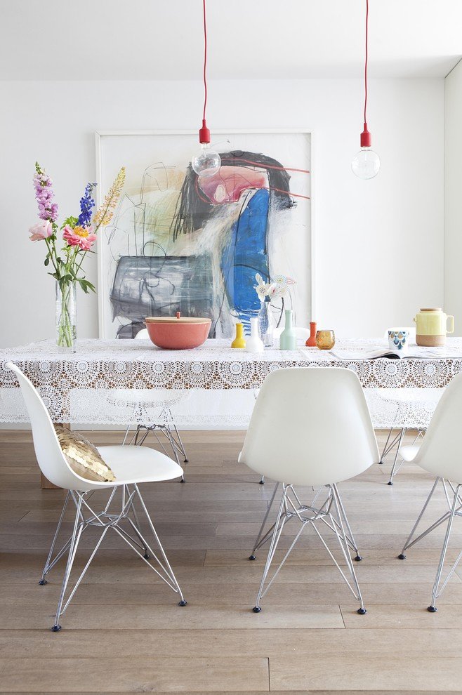 mid century dining room idea wire legs side chairs in white light toned wood floors artistic abstract painting modern bulb pendant lamps