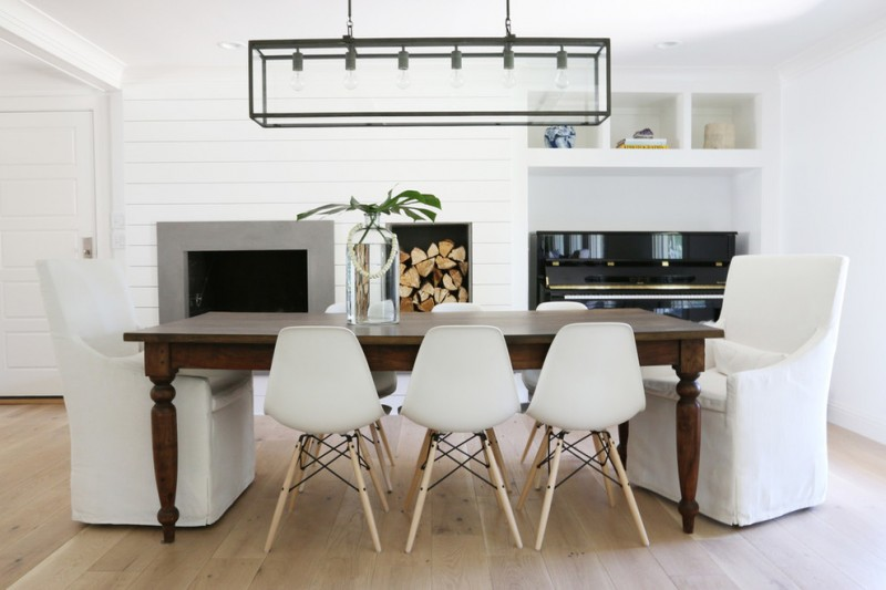 mid century modern dining room white molded plastic chairs with wood legs dark finishing wood table white chair slipcovers standard fireplace stainless steel kitchen appliances industrial pendant
