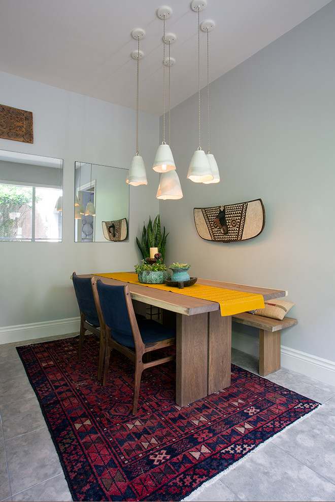 mid century modern dining room wood dining chairs with dark blue covers wood dining table with yellow table skirt wood bench multicolored area rug modern white pendants