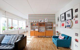 mid century modern living room vintage wood buffet multicolored wall background blue mid century modern sofa medium toned wood floors without finishing