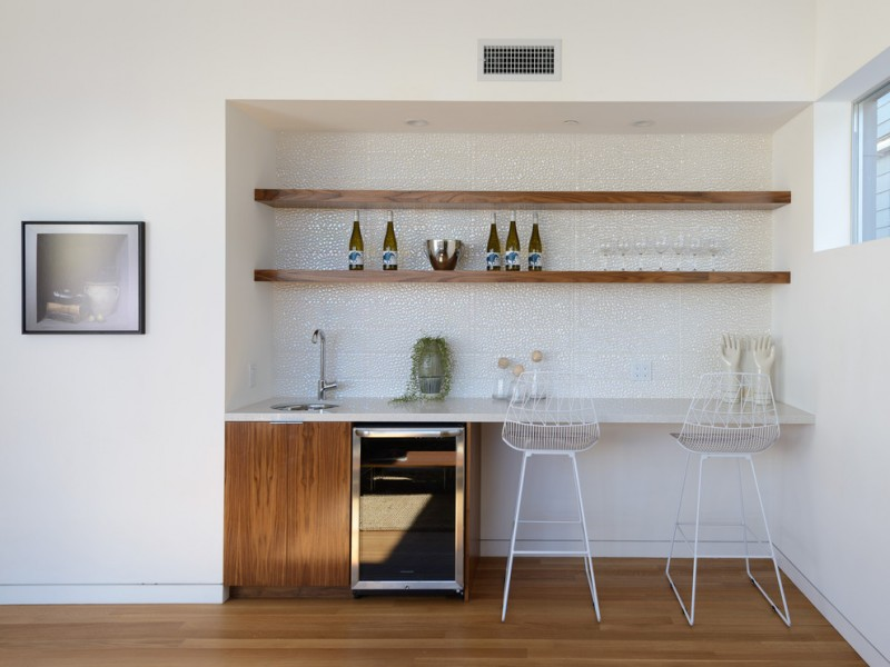 midcentury modern bar idea a pair of white bar stools white countertop wood flat panel cabinets stainless steel appliance two rows of wood shelf mounted on wall medium toned wood floors white walls