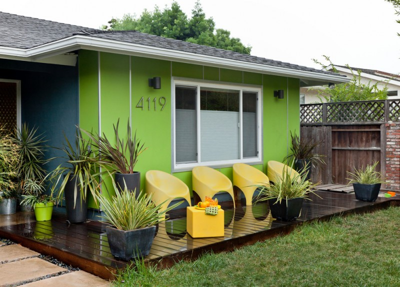 midcentury modern exterior and decking idea green exterior walls with silver vertical lines white trimmed exterior windows yellow outdoor chairs yellow side table dark planters