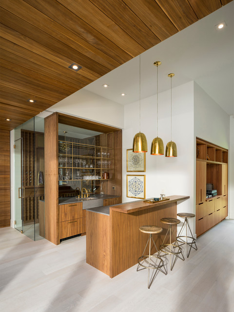 midcentury modern home bar kitchen grey laminated countertop wooden wine rack with glass panel round top bar stools gold toned pendant lamps white finishing wood floors white walls exposed wood ceilin