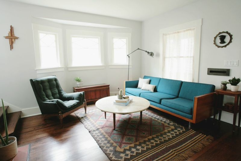 midcentury modern living room turquiso sofa dark green armchair dark toned wood floors traditional area rug