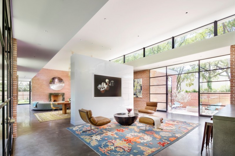 midcentury modern open concept living room with concrete room partition multicolored area rug brown leather chairs dark round top center table dark laminated floors