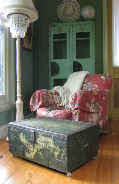 shabby chic living room idea vintage style chair slipcover with flower motifs suitcase center table medium toned wood floors