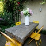 Shabby Chic Outdoor Dining Furniture Set Hardwood Dining Table Chic Yellow Metal Chairs Large Ceramic Vase With Vivid Flowers