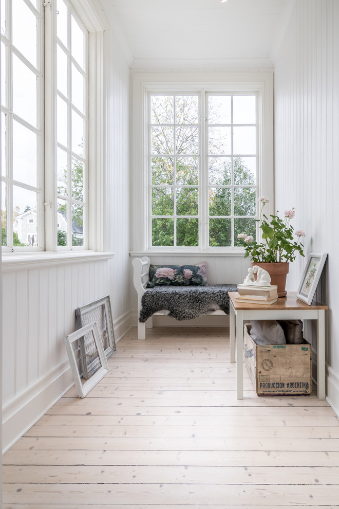 small farmhouse sunroom white vertical siding walls small bench behind the wall small side table whitewashed wood floors boxcars ornaments leaning on walls