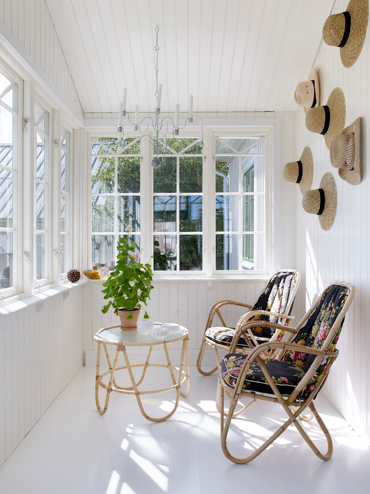 small farmhouse sunroom white wood siding walls white trimmed windows hat ornaments on walls white floors hair pin legs bamboo chairs and table
