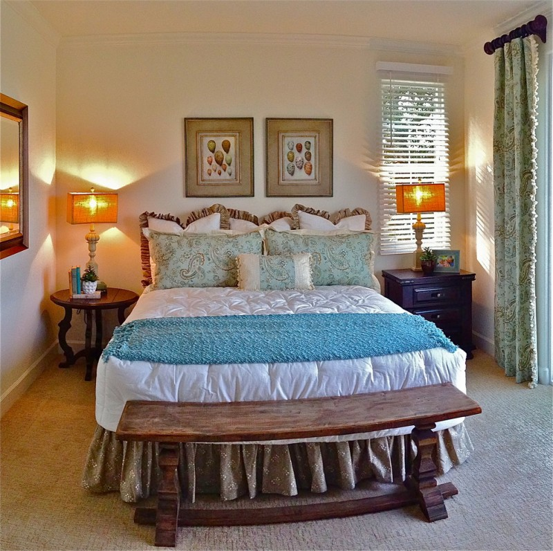small mediterranean master bedroom wood bed bench wood round top bedside table smaller wood dresser beige carpeted floors