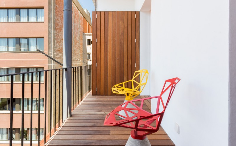 small scandinavian style balcony wood decking black metal railings vertical siding wood wall red and yellow chairs