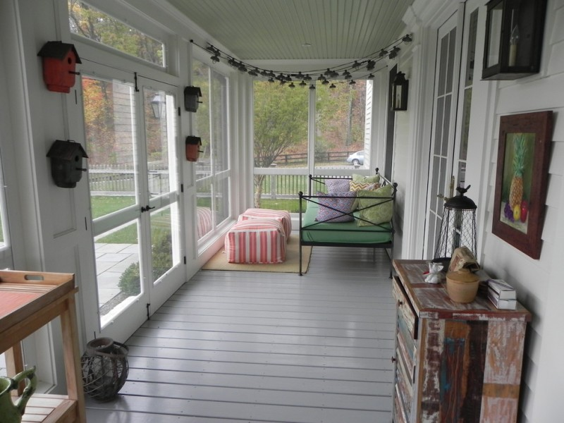 small screened porch thin constructed metal daybed colorful throw pillows colorful & stripped ottoman tables white wood siding floors antique wood display cabinets